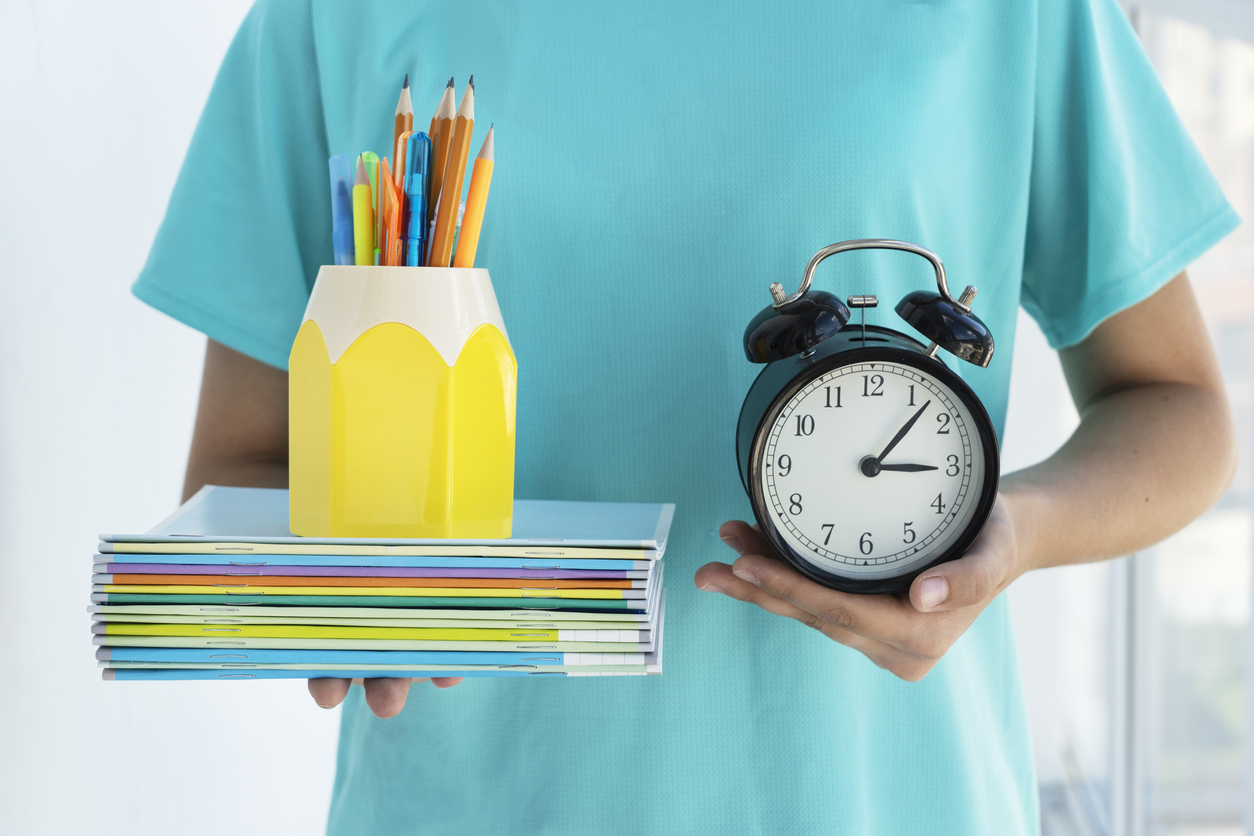close up image of school girl holds alarm clock and school supplies in her hands on light background. Copyspace. Back to school concept, beginning of school year. Manage activities on time.