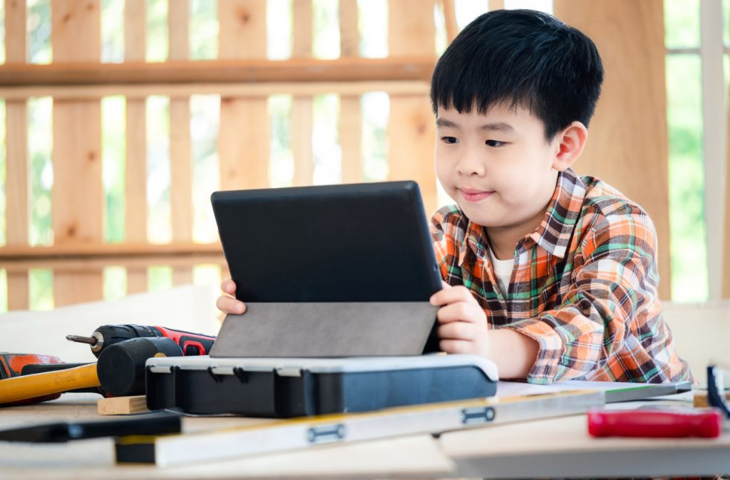 Young Asia boy wearing a shirt and sitting at the table at home and see the tablet. Many equipment tools (hammer, screwdriver, saw) on the table. Carpenter and education concept. Concentrate on tablet