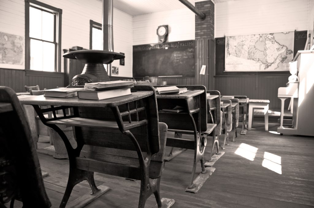 In sepia, a student's view towards the front of a 110 year old one room rural school. Restored