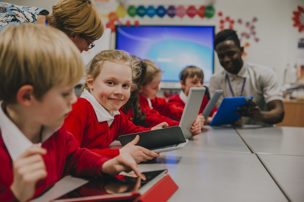 Primary school children are in the ckassroom, learning about and using digital tablets. One of the girls is smiling at the camera.