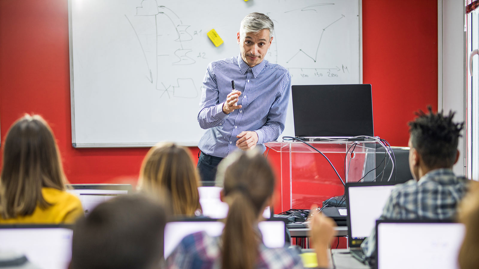 Image featuring a teacher with pupils in a classroom..